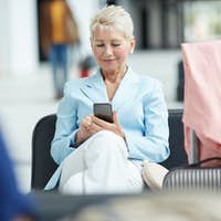 Blond woman using gadget in airport