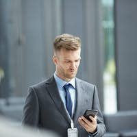 Business forum speaker checking phone