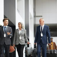 Company managers with luggage in airport