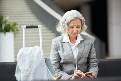 Gray-haired lady checking messenger in airport