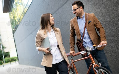 Happy business colleagues talking and walking in the city outdoor