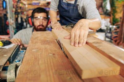 Carpenters cutting wooden plank