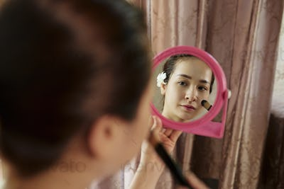 Pretty woman applying foundation