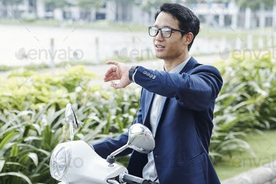 Businessman riding on scooter