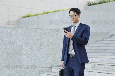 Texting young businessman