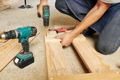 Carpenter using electric screwdriver
