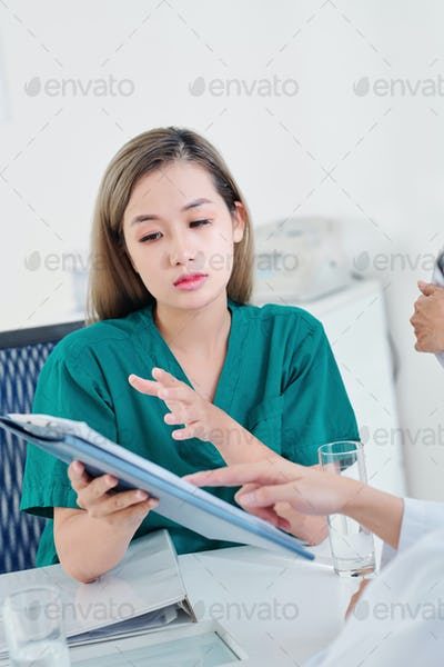 Nurse discussing document with colleague