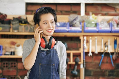 Female carpenter making phone call
