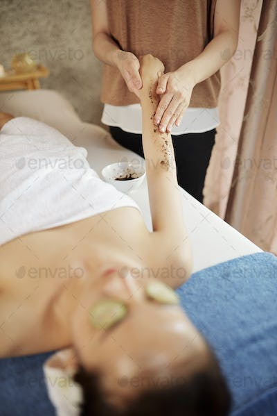 Cosmetologist scrubbing body of client