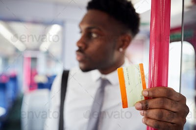 Businessman Standing In Train Commuting To Work Holding Ticket