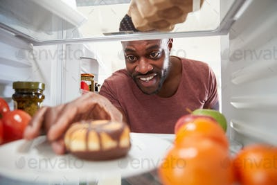 View Looking Out From Inside Of Refrigerator As Man Opens Door And Reaches For Unhealthy Donut