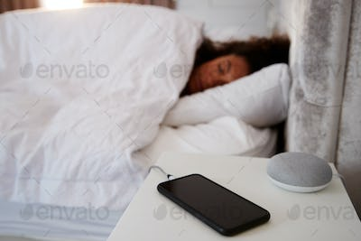 Woman Asleep In Bed With Mobile Phone And Voice Assistant On Bedside Table