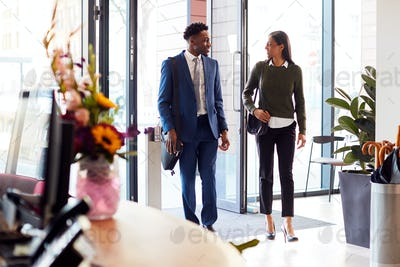 Businessman And Businesswoman Arriving For Work At Office Walking Through Door