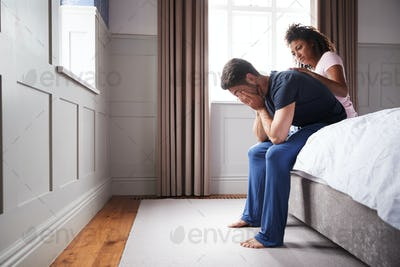Woman Comforting Man Wearing Pajamas Suffering With Depression Sitting On Bed At Home