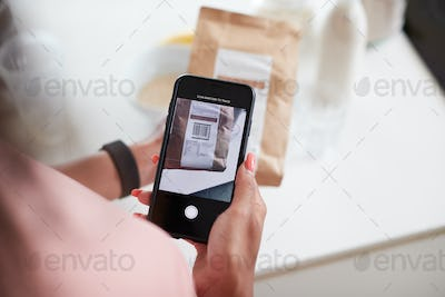 Woman Wearing Fitness Clothing Scanning QR Code On Food Packaging To Find Nutritional Information