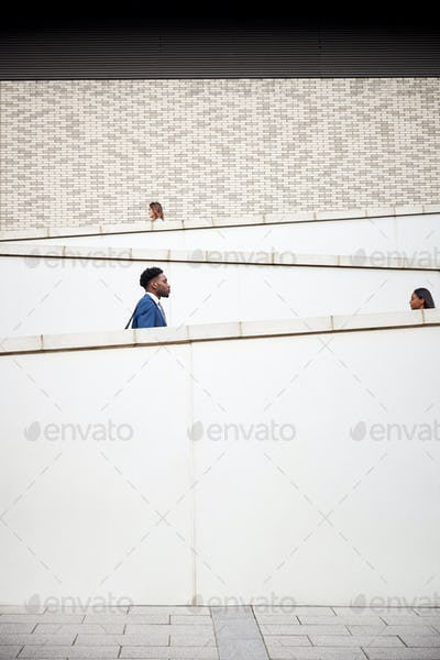 Graphic Shot Of Commuters Walking To Work Along Concrete Walkway Outside Building