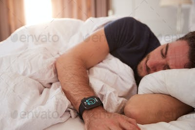 Man Asleep In Bed Wearing Smart Watch As Sun Breaks Through Curtains