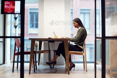 Businesswoman Working On Laptop At Desk In Meeting Room