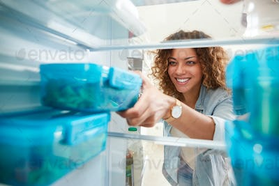 View Looking Out From Inside Of Refrigerator As Woman Takes Out Healthy Packed Lunch In Container