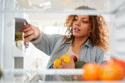 View Looking Out From Inside Of Refrigerator As Woman Opens Door And Packs Food Onto Shelves
