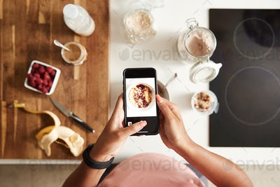 Overhead Shot Of Woman Taking Picture Of Healthy Breakfast On Mobile Phone At Home After Exercise