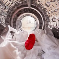 View Looking Out From Inside Washing Machine With Red Sock Mixed With White Laundry
