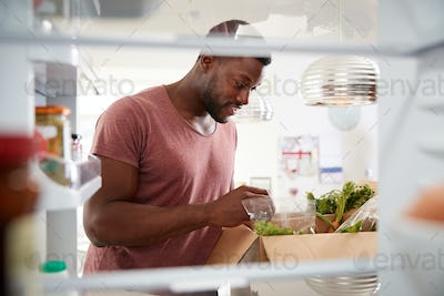 View Looking Out From Inside Of Refrigerator As Man Unpacks Online Home Food Delivery
