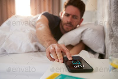 Man Waking Up In Bed Reaches Out To Turn Off Alarm On Mobile Phone