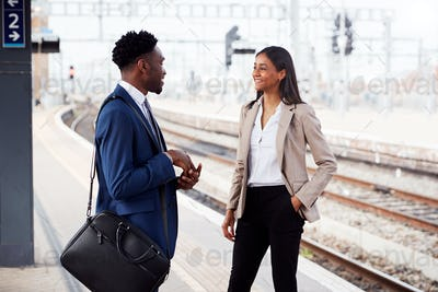 Businessman And Businesswoman Commuting To Work Talking On Railway Platform Waiting For Train