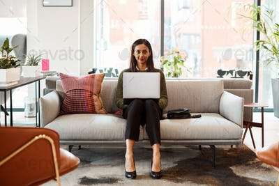 Portrait Of Businesswoman Sitting On Sofa Working On Laptop At Desk In Shared Workspace Office