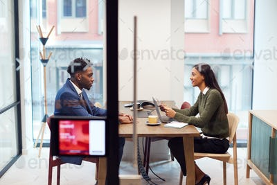 Businesswoman Interviewing Male Job Candidate In Meeting Room
