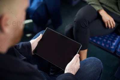 Close Up Of Male Passenger Sitting In Train With Digital Ticket On Tablet Computer