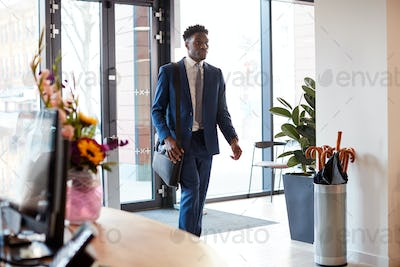 Businessman Arriving For Work At Office Walking Through Door