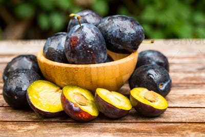 Fresh ripe plums and halves in wooden bowl close