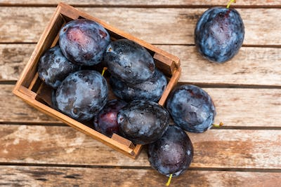 Fresh ripe plums in wooden box top view