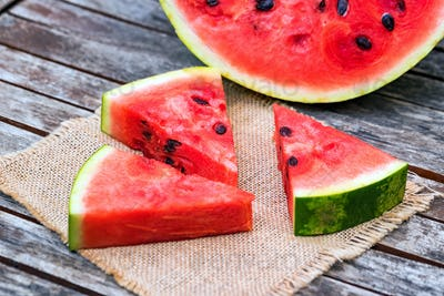 Slices and half of fresh watermelon on wooden board