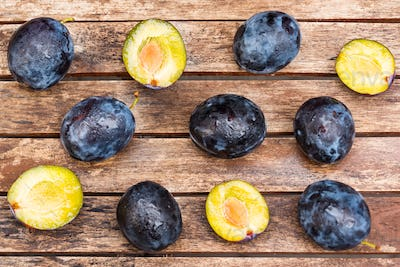 Fresh ripe plums and halves on wooden background