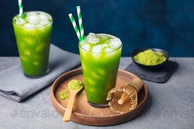 Matcha, Green Ice Tea in Tall Glass on Wooden Plate. Grey stone Background. Copy space.