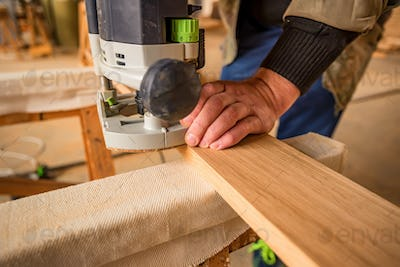 Man processing wood with router in a workshop