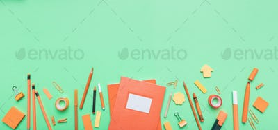 Flat lay of school stationery on green background
