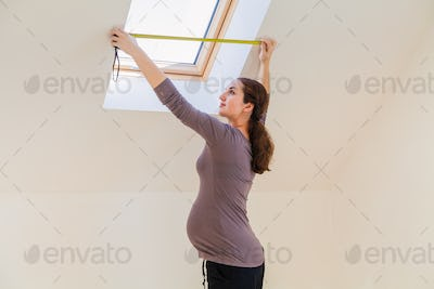 Pregnant Woman with a measure tape in the children's room