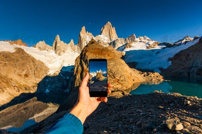 Taking a photo of mountains on a smartphone. Patagonia