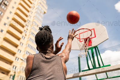 Rear view of young African basketball player throwing ball in basket