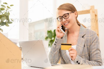 Pretty well-dressed businesswoman talking to online shop manager on mobile phone