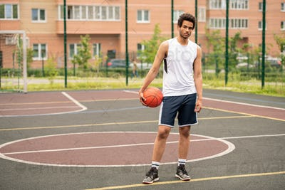 Young athlete with ball standing on racetrack of basketball court