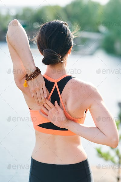 Rear view of fit woman with hair bun contemplating lake