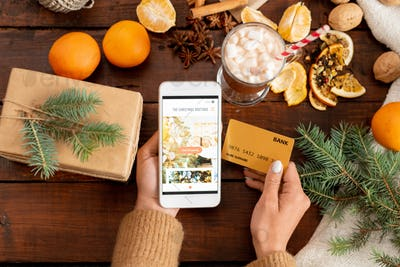 Overview of human hands with smartphone and credit card among xmas stuff