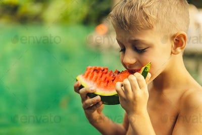 Happy boy eating watermelon