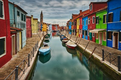 Canal with boats with the colored houses of Burano
