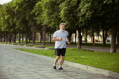 Senior man as runner with armband or fitness tracker at the city's street